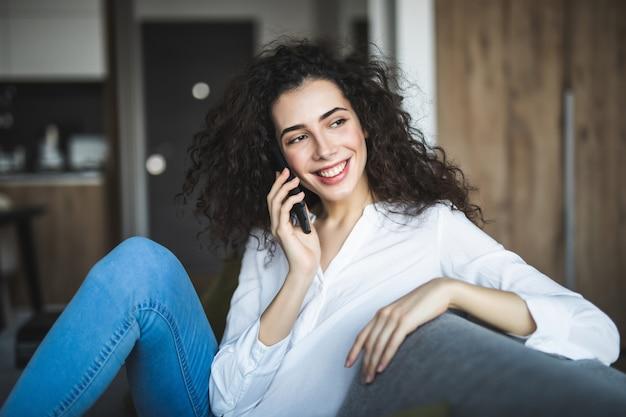 Jonge vrouw met behulp van mobiele telefoon zittend op de bank thuis