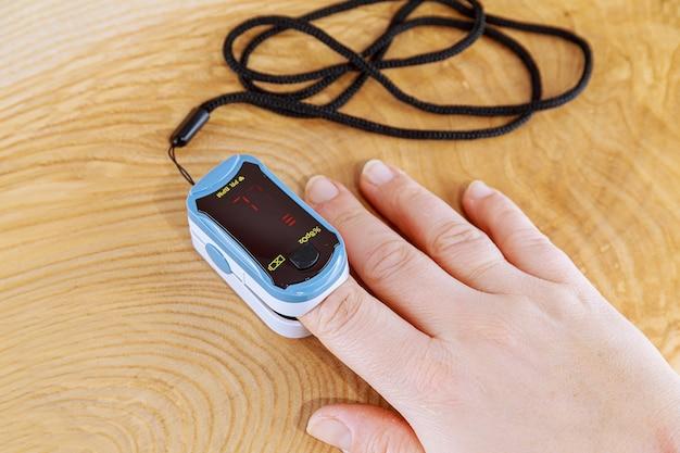 Jonge vrouw met behulp van pulsoxymeter om zuurstofverzadiging, behandeling thuis te meten