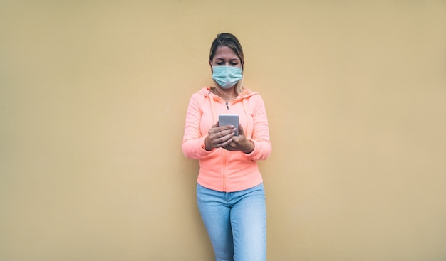 Jonge vrouw met behulp van slimme mobiele telefoon app buiten tijdens covid-19 perion dragen veiligheidsmasker