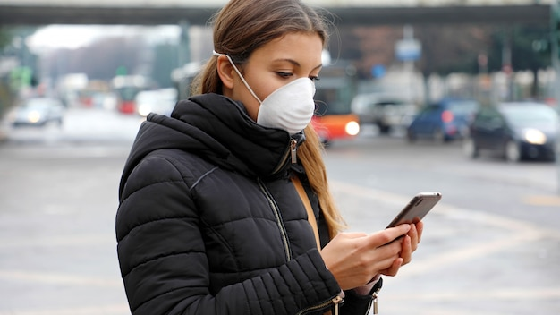 Jonge vrouw met behulp van slimme telefoon in de stad met gezichtsmasker vanwege luchtverontreiniging, deeltjes of griepvirus, influenza, coronavirus