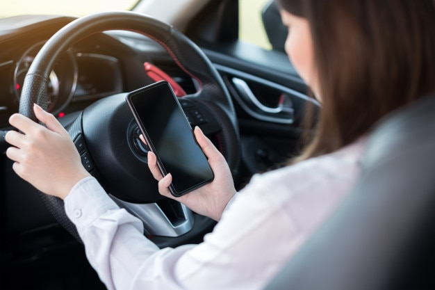 Jonge vrouw met behulp van slimme telefoon tijdens het besturen van een auto