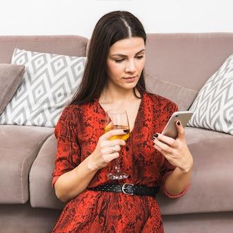 Jonge vrouw met behulp van slimme telefoon wijnglas in de hand te houden