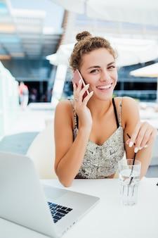 Jonge vrouw met behulp van smartphone bij buiten coffeeshop.