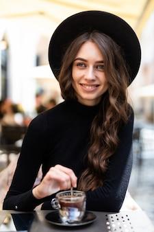 Jonge vrouw met behulp van smartphone en laptop buiten koffie drinken