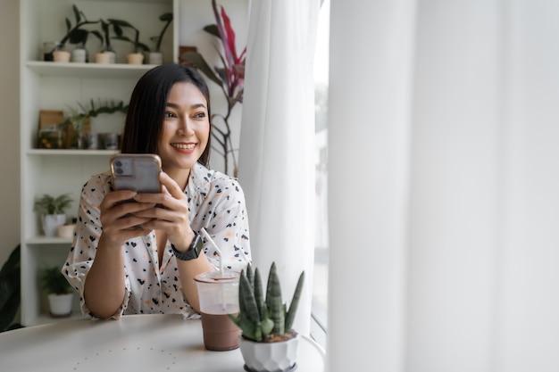 Jonge vrouw met behulp van smartphone in café