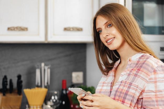 Jonge vrouw met behulp van smartphone in de keuken close-up
