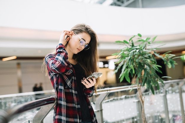 Jonge vrouw met behulp van smartphone in winkelcentrum