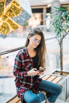 Jonge vrouw met behulp van smartphone op bankje in winkelcentrum