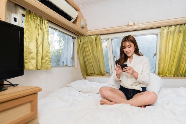 Jonge vrouw met behulp van smartphone op bed van een camper rv busje camper