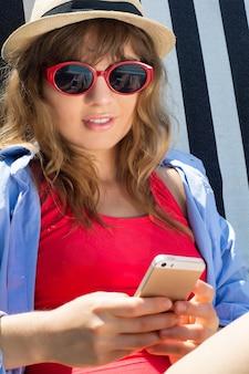 Jonge vrouw met behulp van smartphone op strandstoelen.