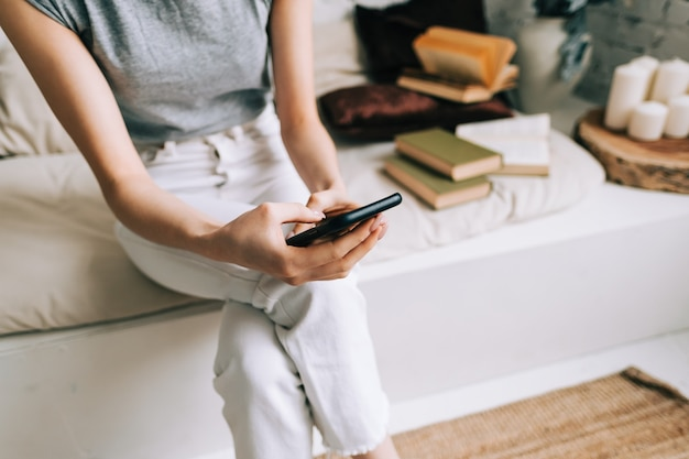 Jonge vrouw met behulp van smartphone terwijl het rusten op een bank thuis