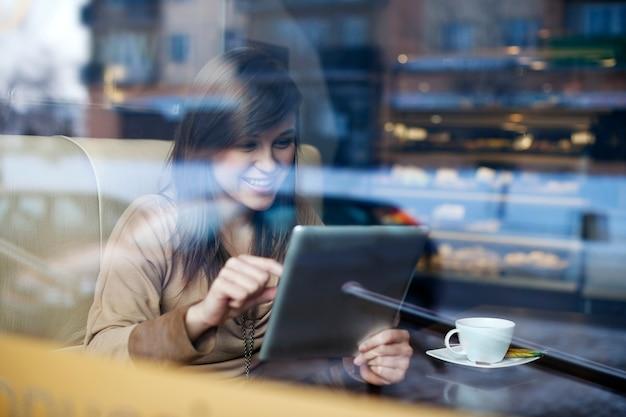 Jonge vrouw met behulp van tablet in coffeeshop
