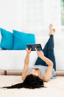 Jonge vrouw met behulp van tablet op de vloer