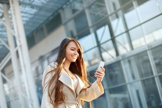 Jonge vrouw met behulp van telefoon buitenshuis. portret van mooie zakenvrouw met smartphone en kopje koffie in handen in de buurt van office center.