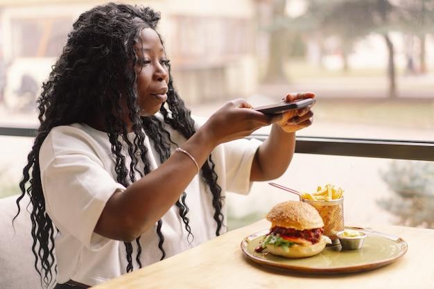 Jonge vrouw met behulp van telefoon in café