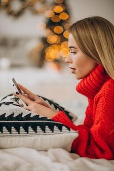 Jonge vrouw met behulp van telefoon op kerstmis