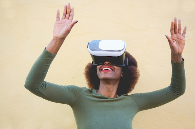 Jonge vrouw met behulp van virtual reality headset met gele muur op achtergrond - afrikaanse vrouw die plezier heeft met nieuwe trendtechnologie - tech, plezier en toekomstconcept - focus op meisjesmond en vr-bril
