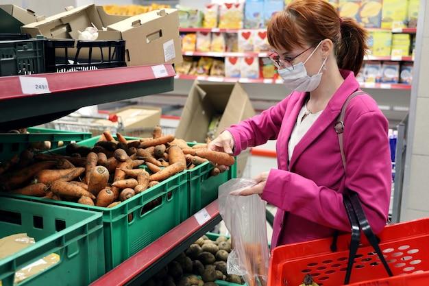 Jonge vrouw met beschermend gezichtsmasker zet rauwe wortelen in boodschappentas