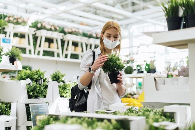 Jonge vrouw met beschermend masker die bloemen koopt in een tuincentrum.
