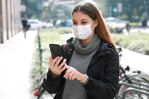 Jonge vrouw met beschermend masker gebruikend smartphone en op vertoning in stadscentrum te kijken