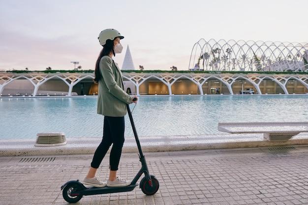 Jonge vrouw met beschermend masker rijden op een elektrische scooter in de stad