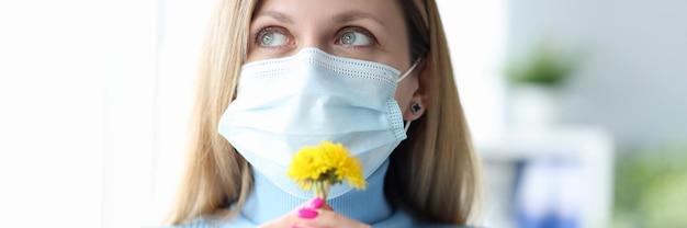 Jonge vrouw met beschermend medisch masker die gele bloem snuift