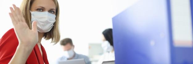Jonge vrouw met beschermend medisch masker zit aan tafel met laptop en zwaait hand in kantoor