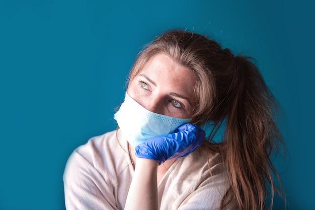 Jonge vrouw met beschermende handschoenen en gezichtsmasker in een huis in quarantaine op zoek verveeld en verdrietig, voor covid-19 coronavirus