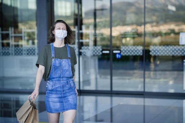 Jonge vrouw met beschermingsmasker tegen coronavirus verlaat het winkelcentrum gelukkig na het doen van haar eerste aankopen na de qurentena door covid.
