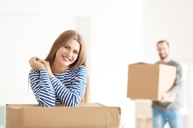Jonge vrouw met bewegende doos in kamer bij nieuw huis