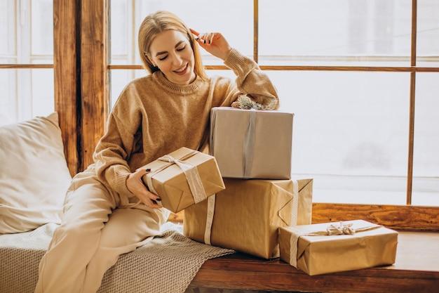 Jonge vrouw met bij het raam zitten met kerstcadeaus