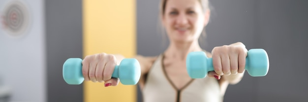 Jonge vrouw met blauwe halters in haar handen close-up thuissport trainingsconcept