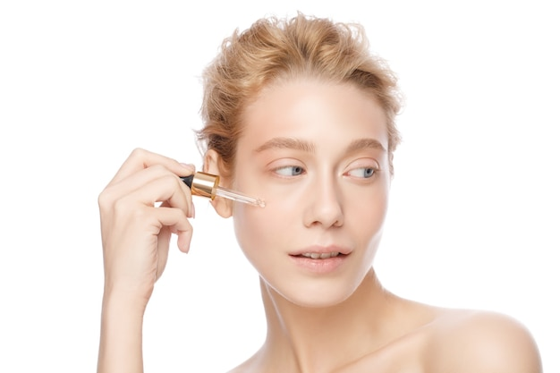 Jonge vrouw met blauwe ogen en blond haar die serum op haar gezicht aanbrengt