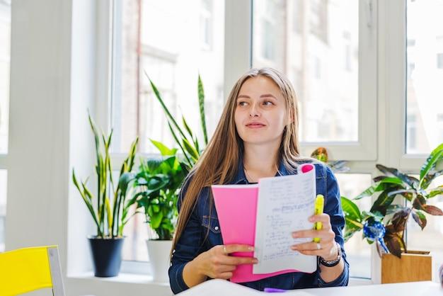 Jonge vrouw met blocnote wegkijken