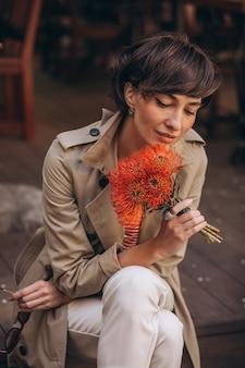 Jonge vrouw met bloemen die op straat zit