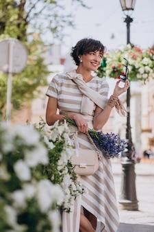 Jonge vrouw met bloemen wandelen in de stad