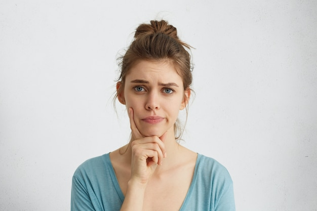Jonge vrouw met blond haar en blauwe ogen die haar wenkbrauwen fronsen, wijsvinger op de kin vasthouden, twijfel en achterdocht, sceptisch over iets. menselijke emoties en uitdrukkingen concept