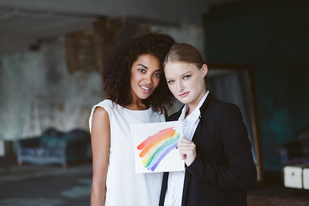 Jonge vrouw met blond haar in zwart pak lgbt-teken in de hand houden met vrij afro-amerikaanse vrouw met donker krullend haar in witte jurk terwijl dromerig samen op huwelijksceremonie