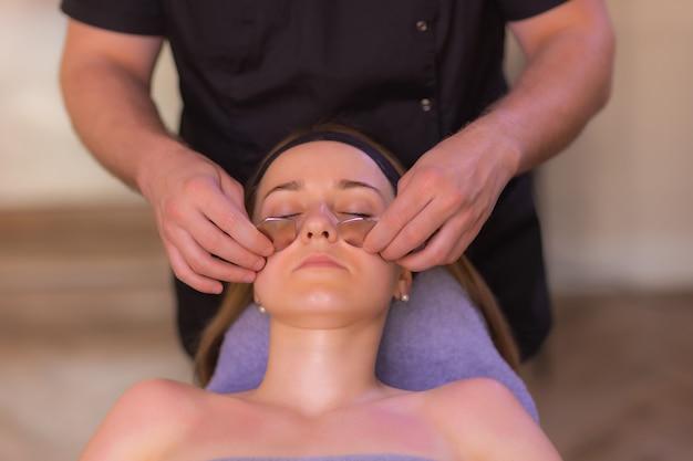 Jonge vrouw met blote schouders die gezichtsmassageapparaat gebruikt terwijl ze geïsoleerd op de bruine achtergrond staat en wegkijkt.
