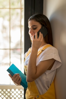 Jonge vrouw met boek dat op telefoon spreekt