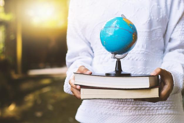 Jonge vrouw met boek en wereldbol op de achtergrond van de natuur en zonnestralen en ruimte voor bijschriften