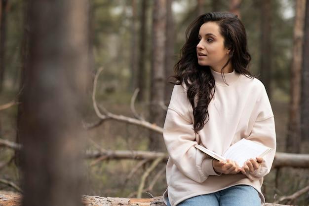 Jonge vrouw met boek in de natuur