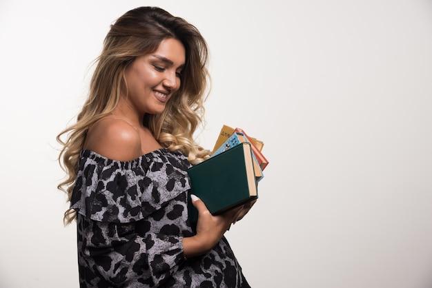 Jonge vrouw met boeken terwijl lachen op witte muur.