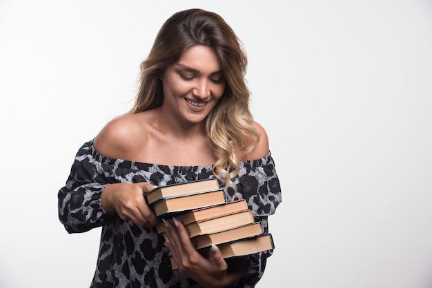 Jonge vrouw met boeken terwijl lachen.