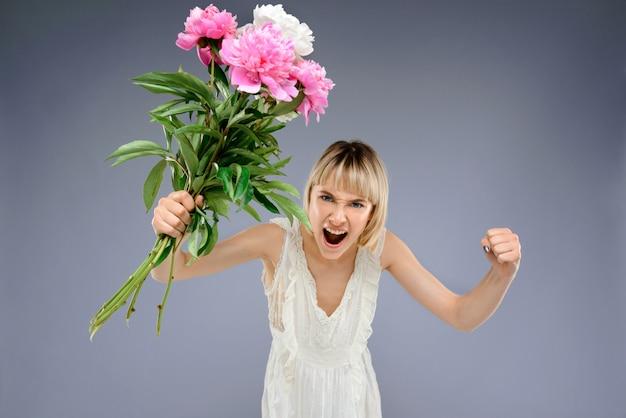 Jonge vrouw met boeket bloemen over grijze backgro