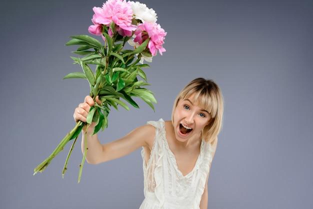 Jonge vrouw met boeket bloemen over grijze muur