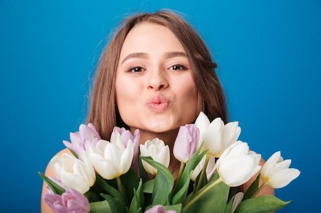 Jonge vrouw met boeket tulpen die een kus stuurt