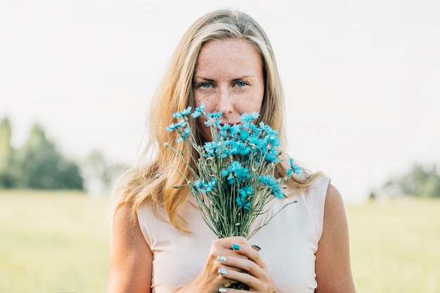 Jonge vrouw met boeket van korenbloemen