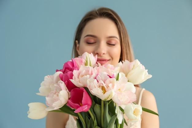Jonge vrouw met boeket van mooie tulpen op groen