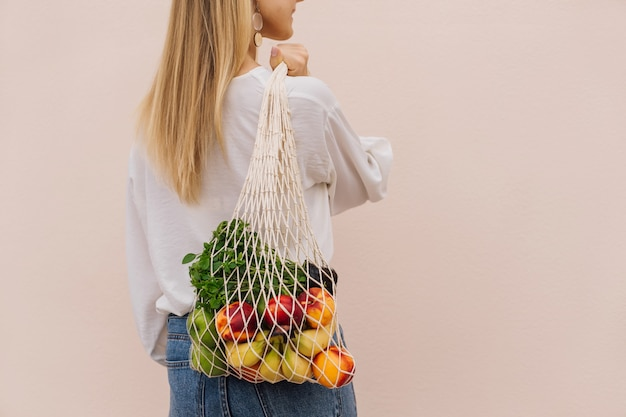 Jonge vrouw met boodschappentas met fruit. herbruikbare eco-tas om te winkelen. geen afval, plasticvrij concept. eco-levensstijl. eco-winkelen. bewuste consumptie. eco-trend. ruimte kopiëren